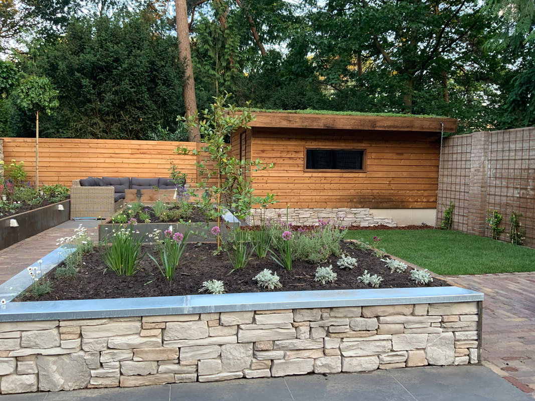 Picture of a garden where different materials were used. On the left side there are flower bng oxes with rusted steel plating and lights on them. In the center there is a square flower box made out of aluminium and small stone cladding. There is a small patch of turf to the right with a wooden shed. The shed roof is covered with plants