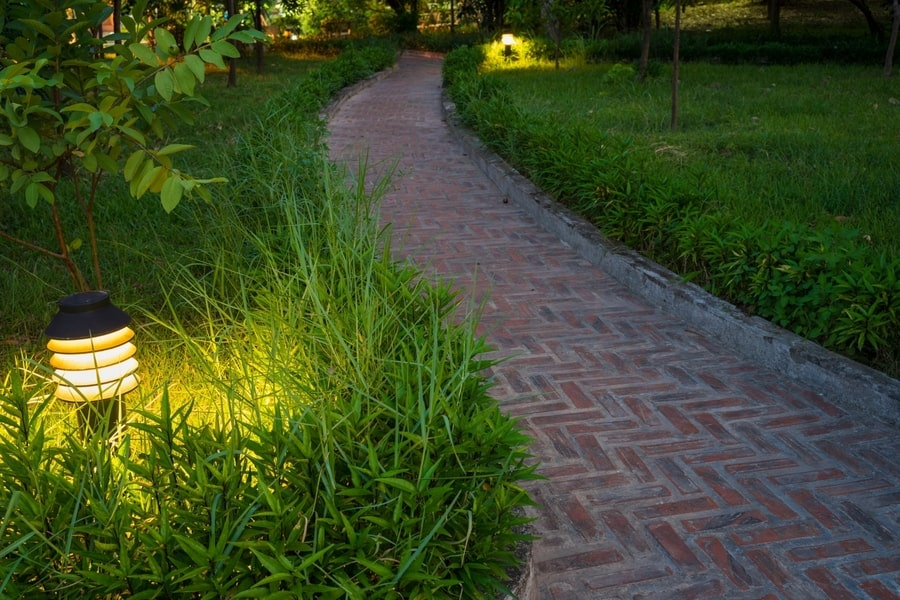 Picture of a herringbone walkway from bricks with exterior path lamps for illumination