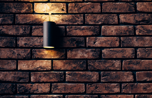 Picture of a dark brick wall where an outdoor wall light is mounted on