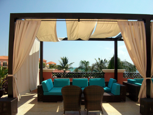 Picture of a roof terrace with decking. On this deck you can see lounge chairs with blue pillows. There is a pergola over the furniture with linnen covers.
