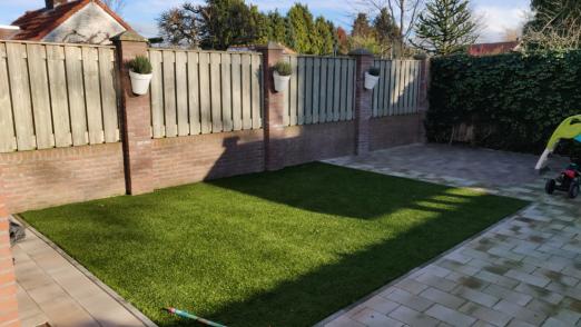 Picture of a garden where a patch of synthetic turf is placed. Around it there is paving and at the back there is a garden wall where the top is replaced with wooden fencing