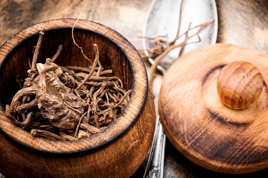 Dry root from the valerian herb in a wooden pot
